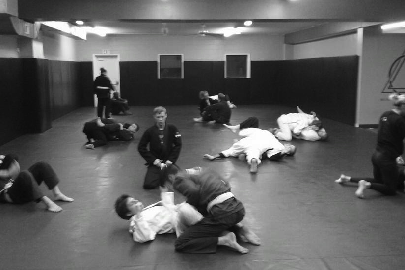 Several pairs of martial artist on the mat practicing Brazilian Jiu Jitsu