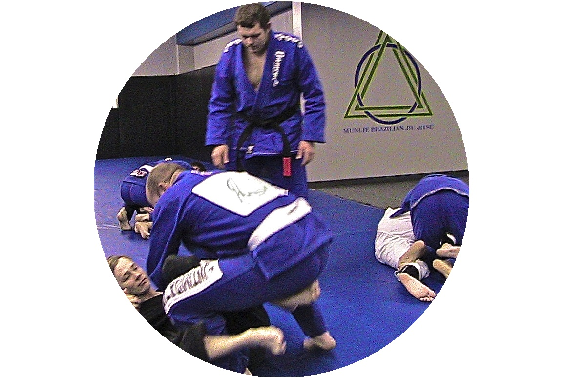 Coach, Max Burt, instructing a small group practicing brazilian jiu jitsu
